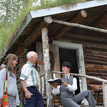 people listen to a reading at the robert service cabin