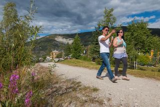 Two people walking along the dike trail in Dawson City