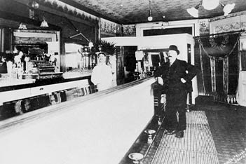 A historic black and white photo of two men in a bar